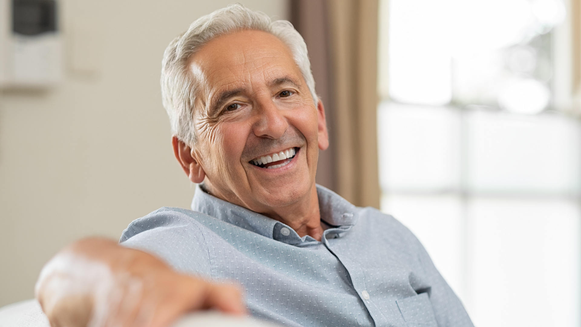 This image shows a seated man, smiling. Catheters for men can be used safely and effectively when properly sized and with the proper style.