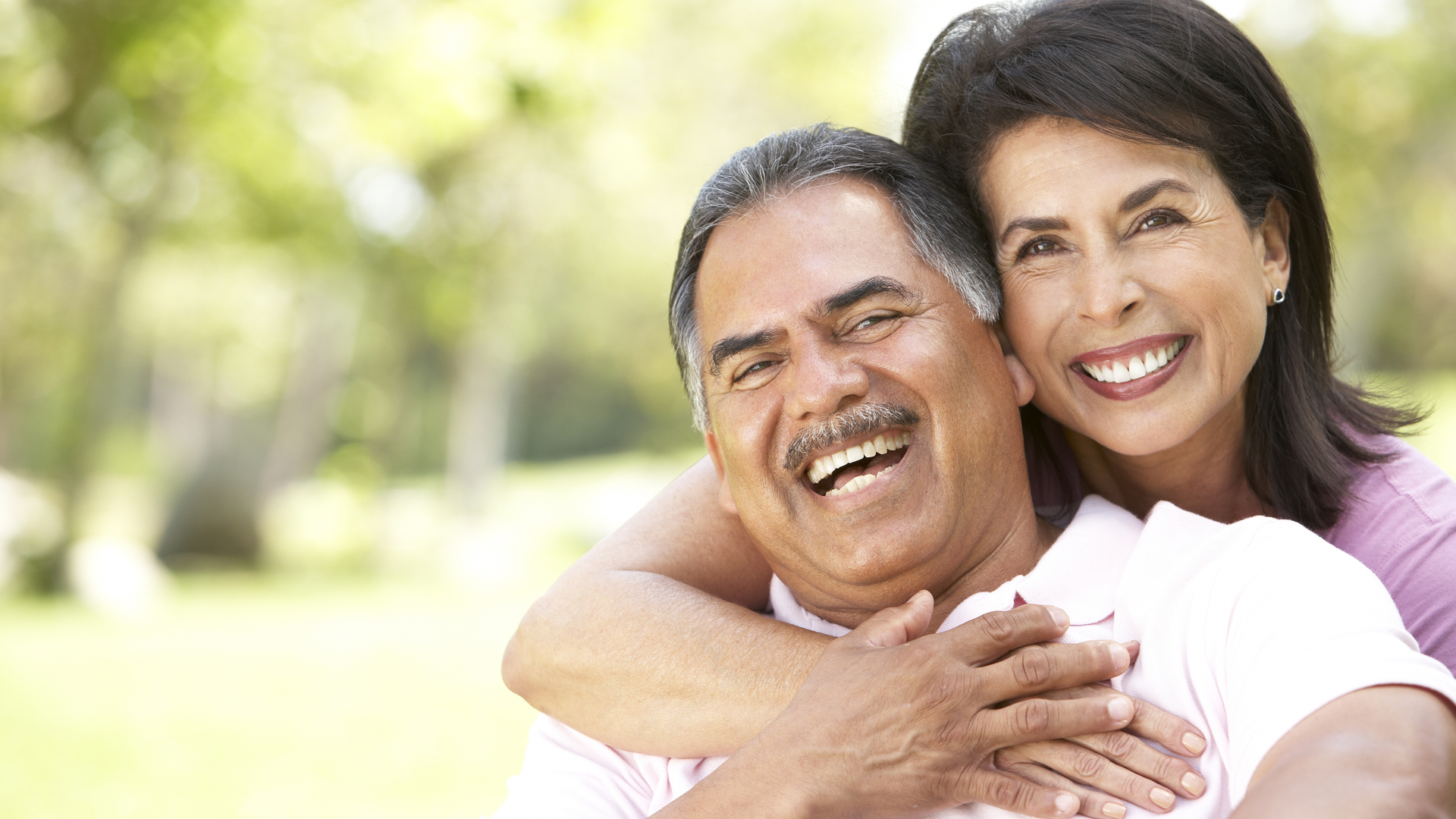 Image of couple hugging and smiling outdoors. Using straight catheters usually allows for a normally active lifestyle.