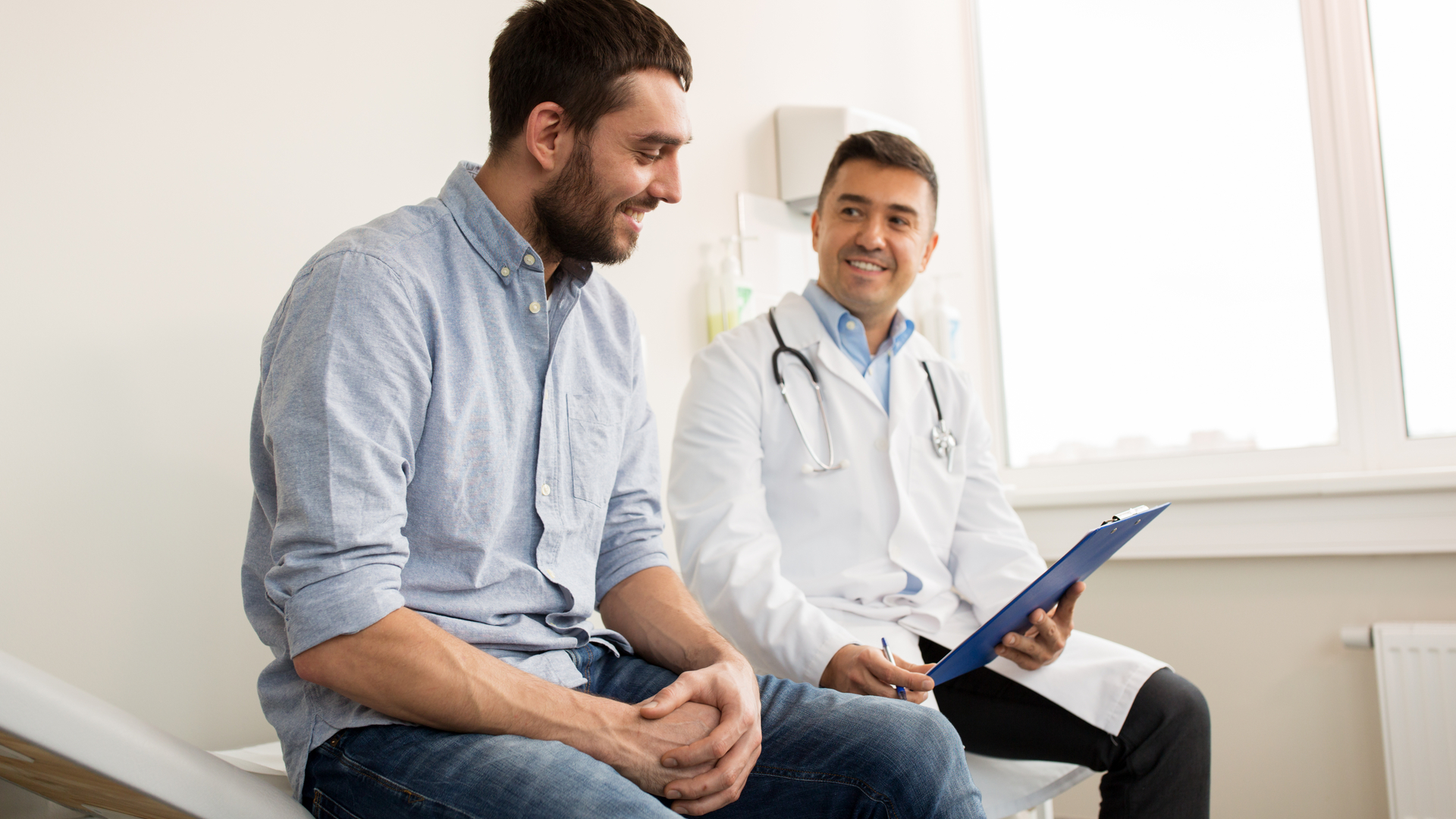 Image showing a man in the doctor's office discussing things with his doctor. Straight catheters should always be discussed with a physician or urologist prior to use.
