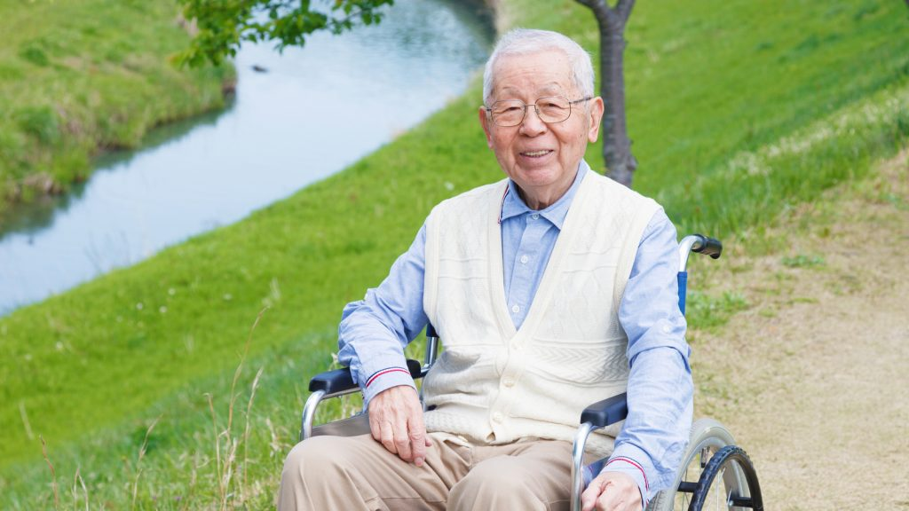 Man sitting in a wheelchair next to a lake. External catheters can be great aids to independence.