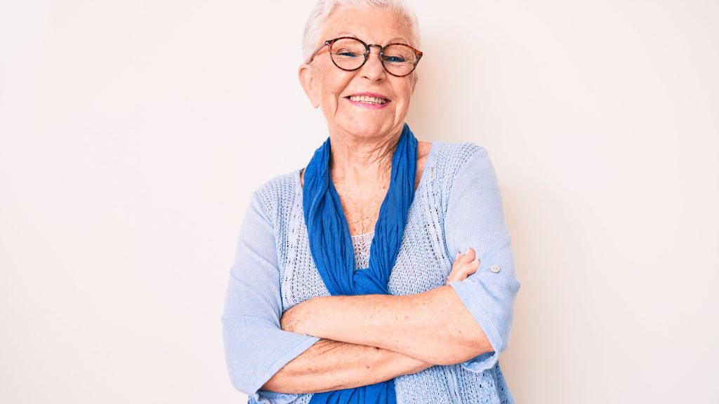 Image of women with glasses, smiling, wearing blue shirt and sweater. Hydrophilic catheters can make it easier to lead a more confident and healthy cathing lifestyle.