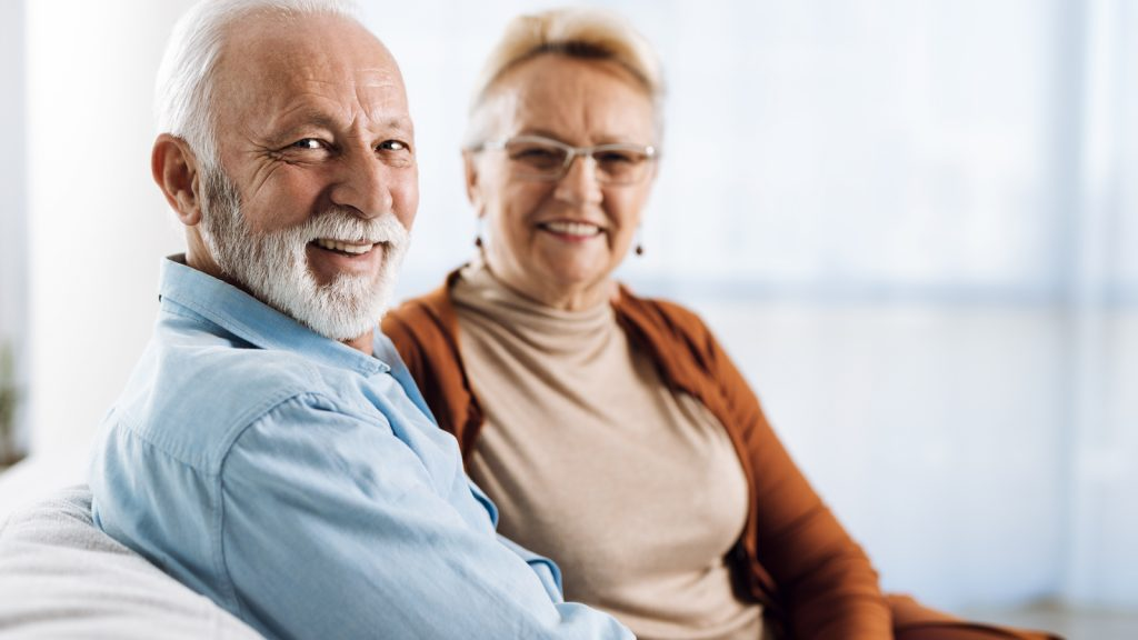 """Smiling couple on couch. If you're wondering """"Where Can I Buy a Catheter?"""" Active Life Medical Can Help."""