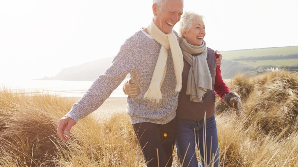 Image showing a couple walking in a field together. Different catheter sizes are used for patients to support proper bladder health.