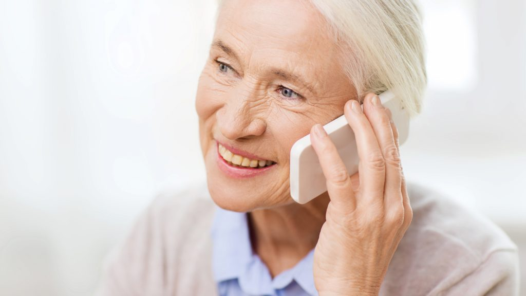 Image showing a woman sitting down on the phone. A catheter kit may help simplify your cathing process.